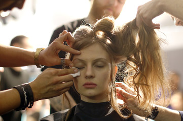 A model has makeup applied and her hair styled backstage before the Just Cavalli Autumn/Winter 2015 /16 collection during Milan Fashion Week