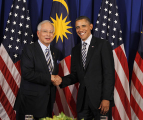 U.S. President Obama shakes hands with Malaysian Prime Minister Najib in Nusa Dua