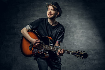 Fashionable hipster blues and jazz acoustic guitar player with tattoos on his arms.