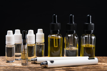 Electronic cigarette on a background of six bubbles with fluids of different flavors