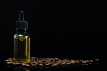 bottle with the aroma of coffee stands in beans on a black background