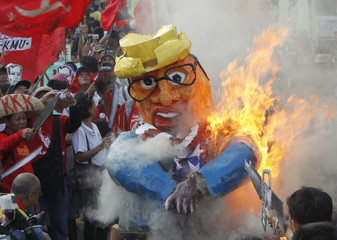 Protesters burn an effigy of the Philippines' President Benigno Aquino during a protest against Aquino's labor policy in Manila