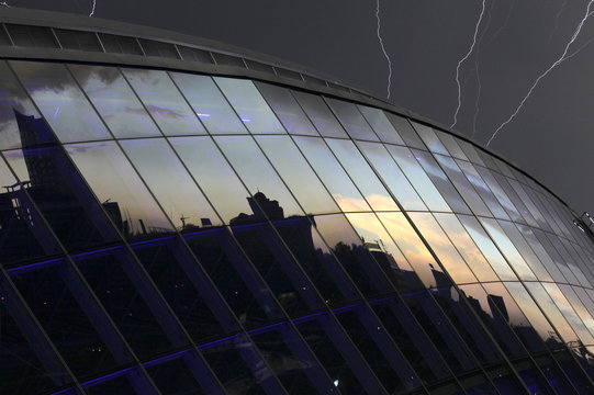 Lightning strikes are seen over the Donbass Arena as the city of Donetsk is seen reflected in glass windows after the Group D Euro 2012 soccer match between Ukraine and France was suspended due to heavy rain in Donetsk