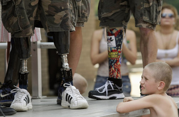 File photo of child looking at prosthetic legs of Wounded Warrior Amputee Softball team members during a Memorial Day Parade in Binghamton