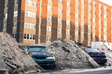 Flooded cars stand underneath piles of sand deposited by heavy machinery working to remove debris deposited by storm surge of superstorm Sandy in Long Beach, New York
