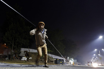 A worker pulls an optic fibre cable to be laid underground along a roadside during the early morning in the western Indian city of Ahmedabad