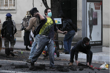 A masked demonstrator throws a piece of asphalt at the French CRS riot police during incidents at the end of a protest demonstration about an airport project in Nantes