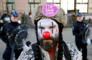 A demonstrator dressed as a clown poses during a protest against TTIP and CETA outside the EU Council in Brussels