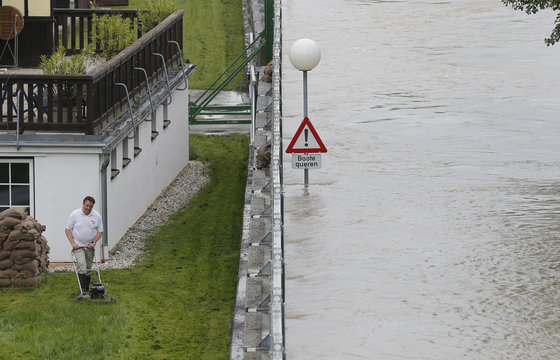A resident mows the lawn in village of Stein-Krems next to the flooded river Danube in Lower Austria