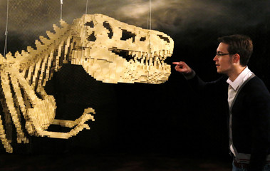 """A visitor looks at the art work titled """"Dinosaur Skeleton"""" during the """"The Art of the Brick"""" exhibition in Brussels"""