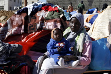 Sudanese refugees from Darfur sit near their tent in an open-ended sit-in in outside the UNHCR office, demanding better treatment and acceleration of their relocation, in Amman