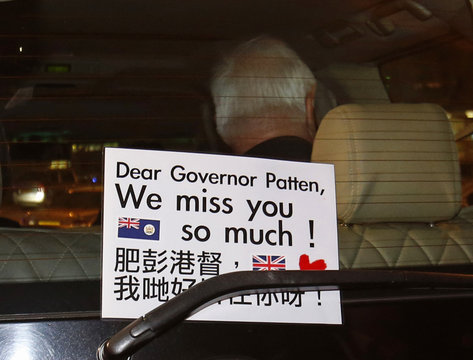 A placard left by supporters is seen on the rear window of the car transporting former Hong Kong Governor Patten as he leaves the Hong Kong Maritime Museum