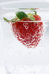 Poster Eclaboussures d eau carbonated water with fresh strawberries, vertical closeup
