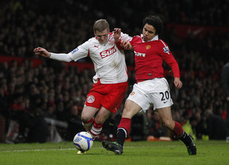 Manchester United's Fabio da Silva challenges Crawley Town's Willie Gibson during their English FA Cup soccer match at Old Trafford in Manchester
