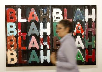 A woman walks past the painting 'Blah, Blah, Blah' by U.S. artist Mel Bochner at the Art Basel art fair in Basel