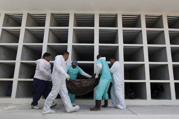 Morgue workers carry a bag containing an unidentified body at Memorial Los Angeles cemetery in Tegucigalpa