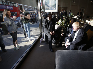 London's Mayor Boris Johnson is photographed by passersby using their mobile phones as he sits in the shop window of a furniture shop whilst campaigning for the local Conservative candidate in Hendon, north London