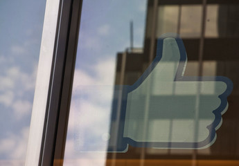 """The Facebook """"Like"""" icon is displayed in a window at the offices of J.P. Morgan in New York City"""