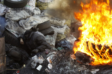 A demonstrator lies near a fire at a barricade erected by anti-government protesters near the site of clashes with riot police, with the air temperatures around minus 20 degrees Celsius, in Kiev