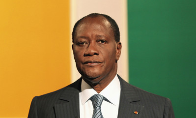 Former Ivory Coast Prime Minister and presidential candidate for the RDR Allassane Ouattara stands in front of Ivorian flag colors  at a television station in Abidjan