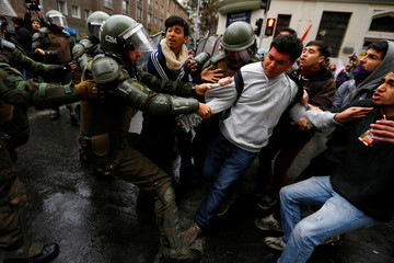 Riot policemen attempt to detain a demonstrator during an unauthorized march of a private university to protest against the government education reform in Santiago