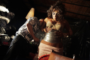 "A transexual contestant wraps duct tape around her body to accentuate her waistline for the beauty peagant ""Miss Trans Nuevo Leon"" at a bar in Monterrey"