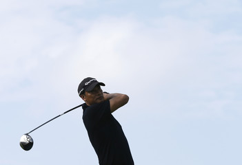 Hong Kong actor Simon Yam tees off on the first hole during the first round of the Mission Hills World Celebrity Pro-Am golf tournament in Haikou