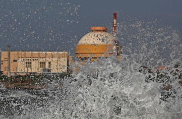 Sea waves hit the rocks as Kudankulam nuclear power project plant is seen in the background in the southern Indian state of Tamil Nadu