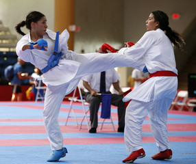 Mendoza of Mexico kicks Urango of Colombia during the 55kg karate finals of the Central American and Caribbean Games in Hormigueros city