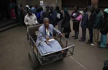 Majika is transported on a pushcart as she leaves after casting her vote in Mbare township outside Harare
