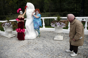 """A woman looks at participants as they pose next to a sculpture during the """"ClownFest"""" International festival of clown art in Moscow"""