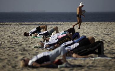 An elderly man walks past people exercising in Copacabana in Rio de Janeiro