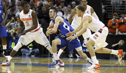 Indiana State Odum secures the ball from Syracuse's Waiters and Jones during their NCAA basketball game in Cleveland