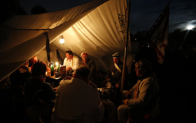 Performers wearing 19th century Saxonian military uniform have dinner in their tent at a bivouac camp for the reenactment of the Battle of the Nations in the village of Markkleeberg