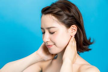 young beautiful woman massaging her neck.