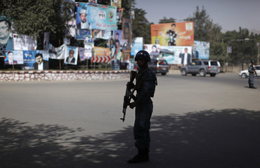 An Afghan policeman keeps watch next to posters of candidates for the parliamentary elections, in Kabul