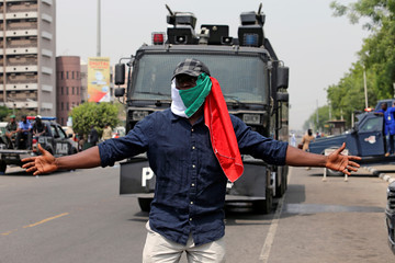 Anti-government protester stands in front of a police truck during a march in Abuja