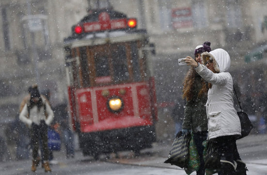 """Pedestrians, with a vintage tram in the background, take a """"selfie"""" as snow falls at the main shopping street of Istiklal in central Istanbul"""