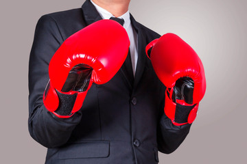 business man puts on boxing gloves.