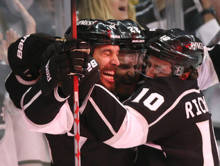 Los Angeles Kings' Lewis is bathed in red light as he celebrates with teammates King and Richards after scoring against the New Jersey Devils during the first period in Game 6 of the NHL Stanley Cup hockey final in Los Angeles