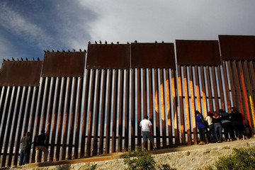 People talk to their relatives across a fence separating Mexico and the United States, in Tijuana, Mexico