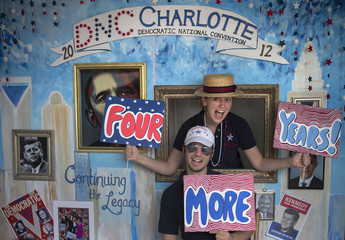 A couple attract customers to take pictures at their photo booth which was set-up at a street festival for convention goers ahead of the Democratic National Convention in Charlotte, North Carolina