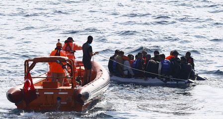 A line is thrown from a Turkish Coast Guard fast rigid-hulled inflatable boat off the shores of Canakkale, Turkey, as refugees and migrants in a dinghy paddle on the Turkish territorial waters of the North Eagean sea