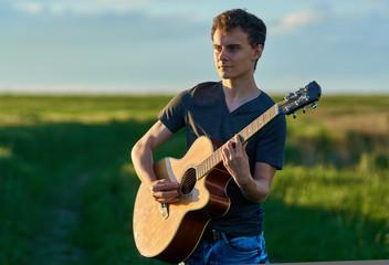 Teenager playing guitar at sunset
