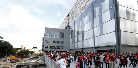 Soccer fans arrive to attend the first test event while construction is still ongoing at the Arena da Baixada stadium in Curitiba
