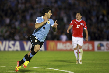Uruguay's xxxx battles for the ball with Chile's xxx during their World Cup qualifying soccer match in Montevideo