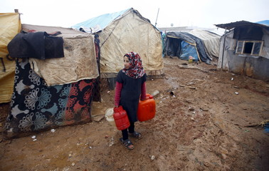 An internally displaced Syrian girl carries water cans at a refugee camp near the Bab al-Salam crossing, opposite the Turkey's Kilis province