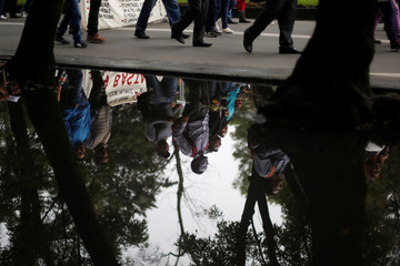 An activist wearing a Guy Fawkes mask is reflected in the water as he takes part during a march against President Enrique Pena Nieto's education reform, with people from civil organizations and the CNTE teachers' union at Reforma avenue, in Mexico City