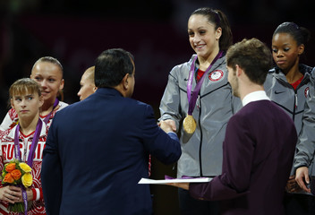Team U.S.A member Jordyn Wieber receives her gold medal as she is watched by team mate Gabrielle Douglas and Anastasia Grishina of Russia during the women's gymnastics team final in London