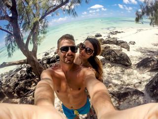 Beautiful young couple taking a selfie on the beach, enjoying their honeymoon. Turquoise ocean water in the background.  on the beach. Turquoise ocean water in the background.